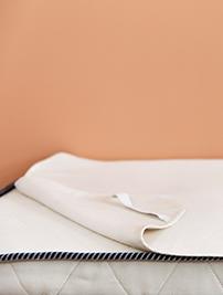 Alèse Le Petit Cosme, posée sur un matelas de la même marque gamme bébé