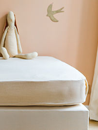 Linge de lit Le Petit Cosme, recouvrant un matelas posé sur un sommier