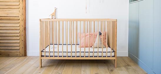 Matelas bébé Le Petit Cosme placé dans un lit à barreaux dans une chambre bébé